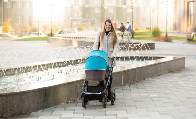 Heureuse jeune mère avec poussette de bébé marchant dans la rue près de la fontaine