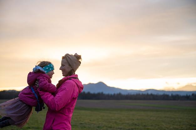 Heureuse jeune mère s'amusant avec sa petite fille dehors dans un pré, la soulevant et la faisant tourner dans une liaison ludique.