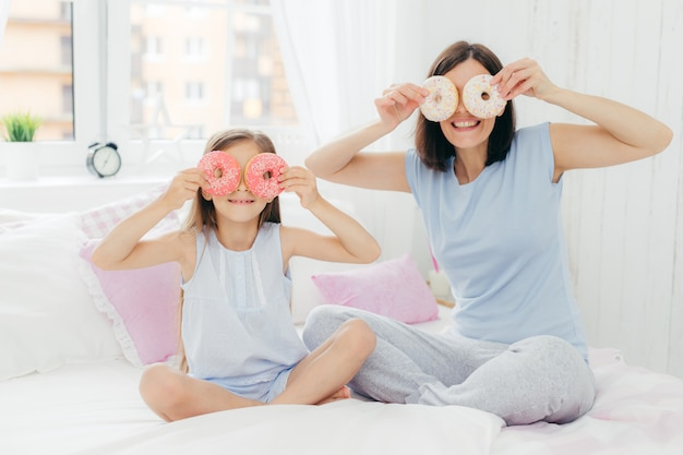 Heureuse jeune mère et sa fille s'amusent ensemble, tenez de délicieux beignets sucrés près des yeux