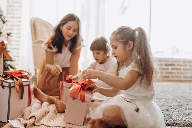 Heureuse jeune mère et ses deux charmantes filles vêtues de jolies robes s'assoient sur le tapis et ouvrent les cadeaux du nouvel an dans la pièce lumineuse et confortable.