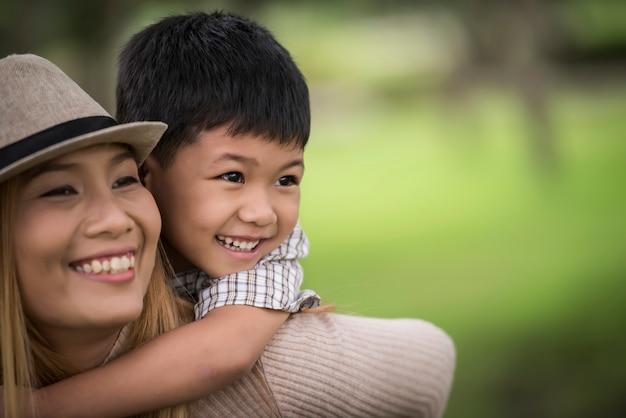 Heureuse jeune mère et son fils, petit garçon qui rit, obtenant une promenade sur le dos.