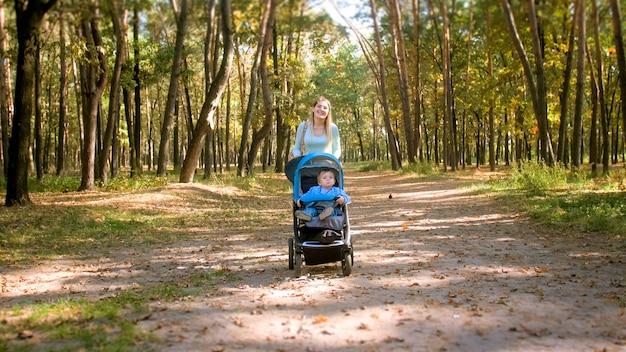 Heureuse Jeune Mère Souriante Avec Poussette Bébé Marchant Sur Le Sentier à La Forêt D'automne. Photo Premium