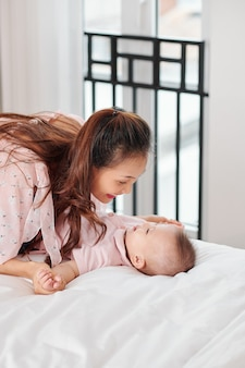 Heureuse jeune mère souriante se penchant sur son mignon petit fils allongé sur un grand lit confortable et lui disant quelque chose