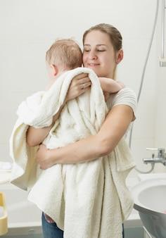 Heureuse jeune mère tenant son bébé après le bain