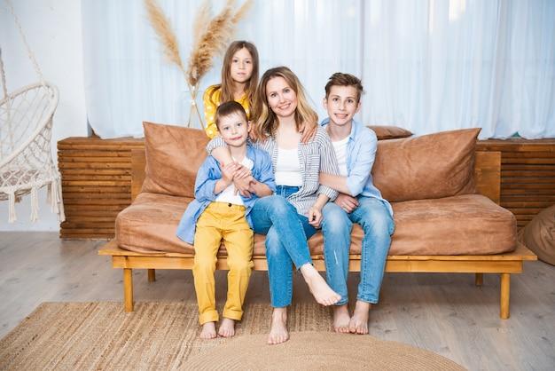 Heureuse jeune mère avec trois enfants assis sur le canapé, la famille appréciant le moment tendre, s'amusant ensemble