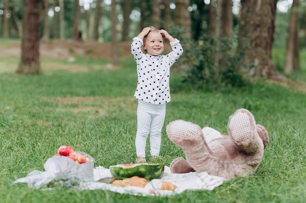 Heureuse jeune petite fille souriante sur pique-nique dans le parc à la journée d'été. le concept de vacances d'été. jour de bébé. passer du temps avec la famille. mise au point sélective