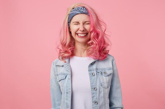 Heureuse jolie dame souriante aux cheveux roses et aux mains tatouées, debout les yeux fermés, largement souriante, vêtue d'un t-shirt blanc et d'une veste en jean.