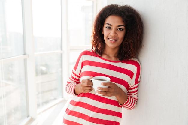 Heureuse jolie femme africaine, boire du café près de la fenêtre