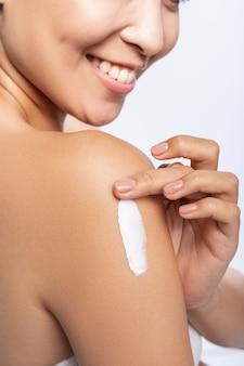 Heureuse jolie femme applique une crème pour les bras