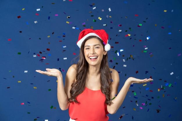 Heureuse jolie femme asiatique célébrer la fête avec des confettis multicolores tombant sur fond de couleur bleue