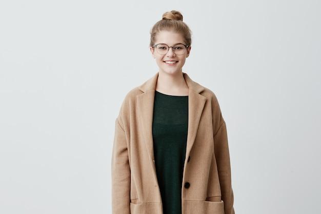 Heureuse jolie femme aux cheveux blonds en noeud, lunettes et peau saine vêtue d'un manteau brun sur un pull vert souriant tout en posant contre le mur de béton. personnes et style de vie