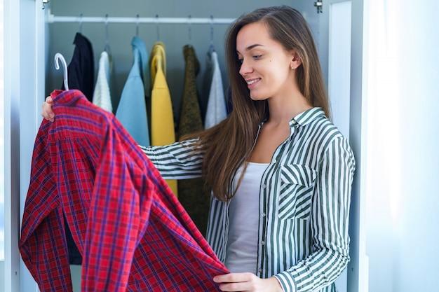 Heureuse jolie femme brune moderne choisissant la tenue du placard avec des vêtements élégants et des trucs pour la maison pour une occasion spéciale