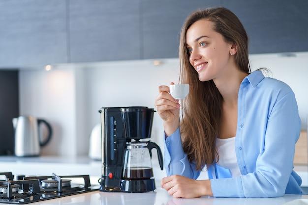 Heureuse jolie femme buvant du café aromatique frais et chaud après avoir préparé du café à l'aide d'une cafetière dans la cuisine à la maison. mélangeur à café et appareils électroménagers pour préparer des boissons chaudes