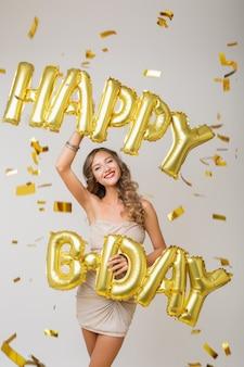 Heureuse jolie femme célébrant son anniversaire dans des confettis dorés