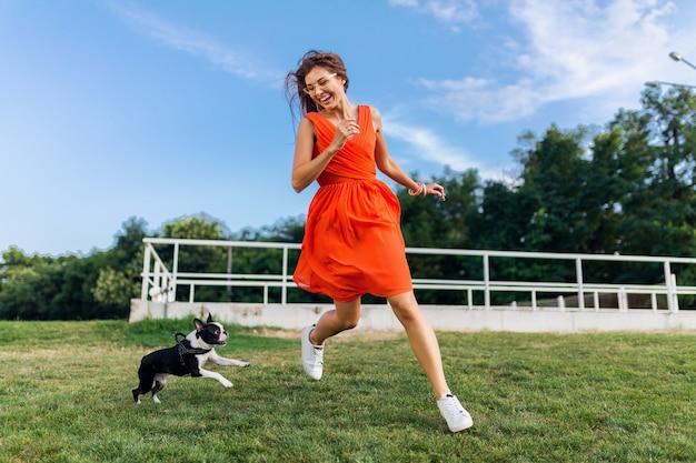 Heureuse jolie femme dans le parc en cours d'exécution avec chien boston terrier, souriant humeur positive, style estival branché, vêtu d'une robe orange, jouer avec un animal de compagnie, s'amuser, vacances de week-end colorées et actives, baskets