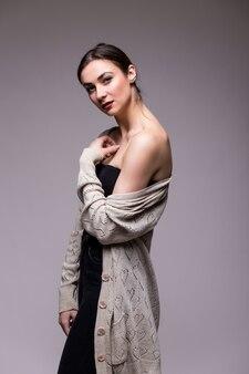 Heureuse jolie femme debout sur gris et regardant la caméra