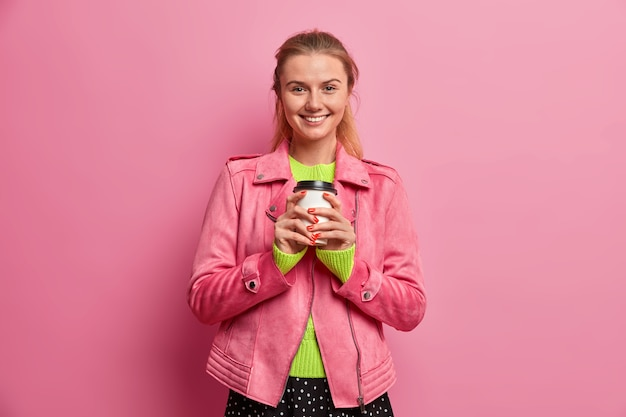 Heureuse jolie femme européenne boit une tasse de café aromatique savoureux, visite le meilleur café à emporter, vêtu d'une veste rose à la mode, apprécie les week-ends, sourit volontiers