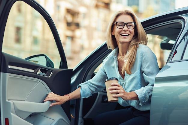 Heureuse jolie femme ou femme d'affaires portant des lunettes tenant une tasse de café et sortir de sa voiture moderne, concept de transport