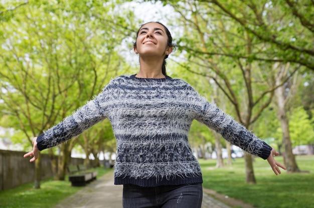 Heureuse jolie femme répandre les mains et marcher dans le parc