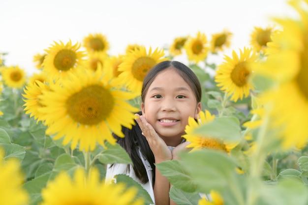 Heureuse jolie fille asiatique souriante avec tournesol,