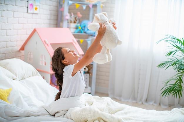 Heureuse jolie fille assise sur le lit dans la chambre de ses enfants et soulève l'ours en peluche.