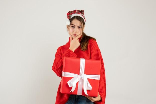Heureuse jolie fille avec bonnet de noel tenant un cadeau lourd mettant la main sur son menton debout sur blanc