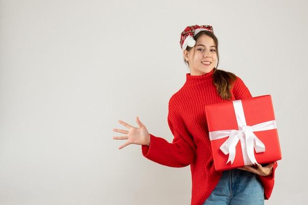Heureuse jolie fille avec bonnet de noel tenant un cadeau et ouvrir sa main debout sur blanc