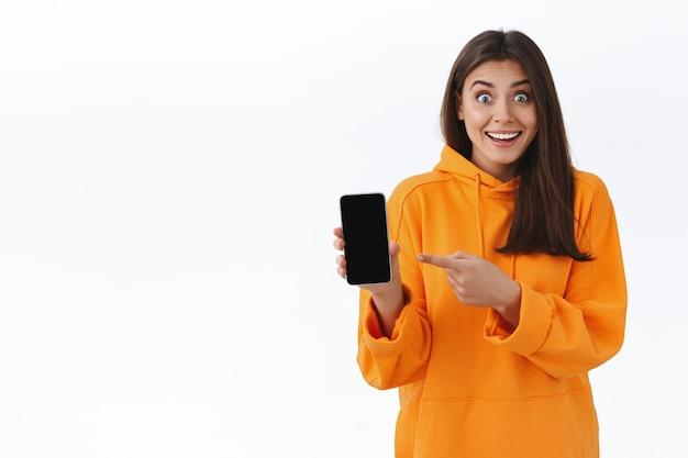 Heureuse jolie fille brune surprise en sweat à capuche orange, tenant un téléphone portable et pointant sur l'écran pour vous montrer un événement génial qui se passe à proximité, veut réserver des billets, vous regarde impressionné