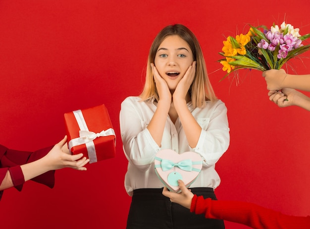 Heureuse, jolie fille caucasienne isolée sur studio rouge