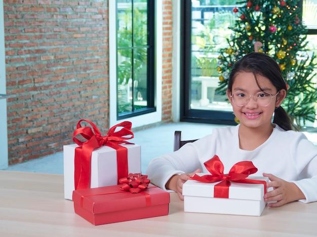 Heureuse jolie fille avec des coffrets cadeaux à la maison avec des décorations festives. joyeux noël heureuse nouvelle année.