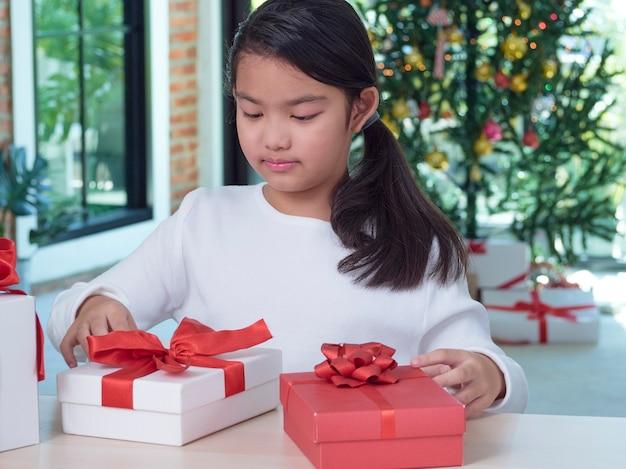 Heureuse jolie fille avec des coffrets cadeaux à la maison avec des décorations festives.