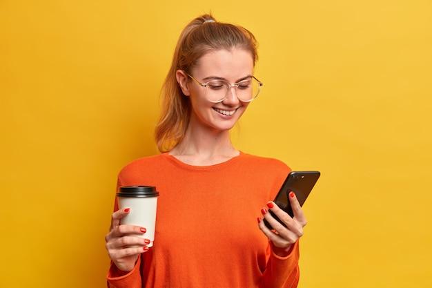Heureuse jolie fille du millénaire télécharge une nouvelle application mobile, boit du café dans une tasse en papier, a un sourire agréable, envoie des sms dans le chat, porte des lunettes optiques, a les cheveux peignés en queue de cheval, surfe sur internet