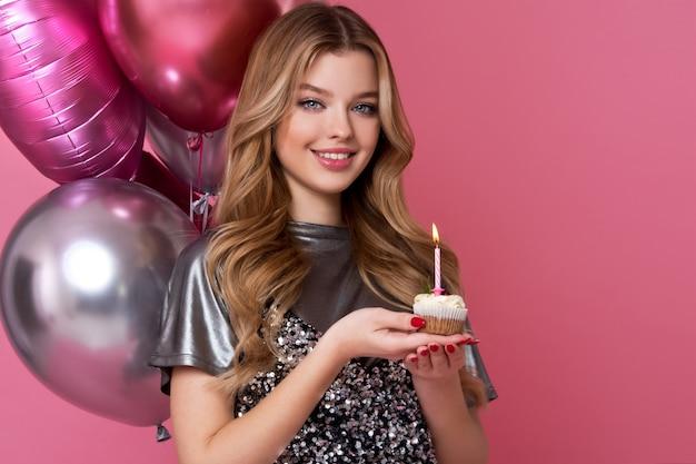 Heureuse jolie fille avec un gâteau à la crème et des ballons roses