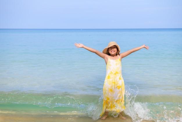 Heureuse jolie fille jouant sur la plage,