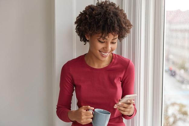 Heureuse jolie fille noire heureuse de développer son propre blog, se réjouit d'avoir de nombreux adeptes