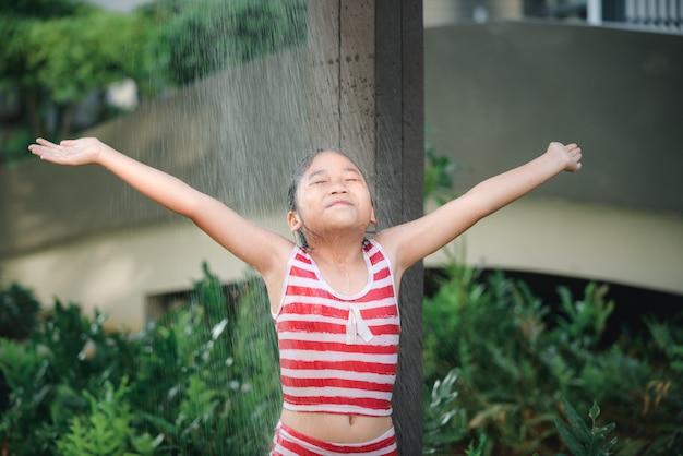 Heureuse jolie fille prenant une douche avant de nager,