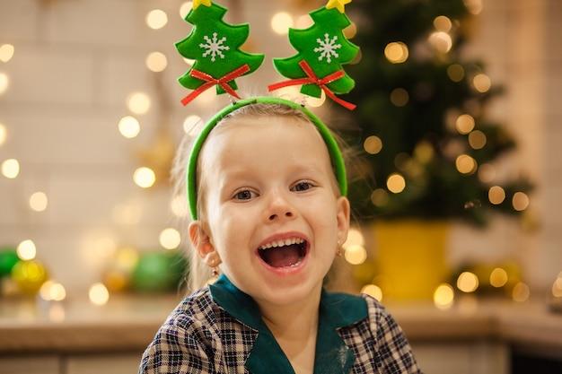 Heureuse jolie fille en pyjama prépare la pâte pour les cookies du nouvel an pour célébrer noël.