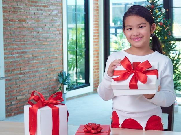 Heureuse jolie fille tenant une boîte-cadeau à la maison avec des décorations de fête. joyeux noël heureuse nouvelle année.