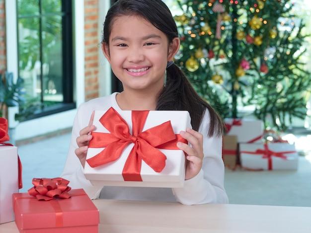 Heureuse jolie fille tenant une boîte-cadeau à la maison avec des décorations de fête.