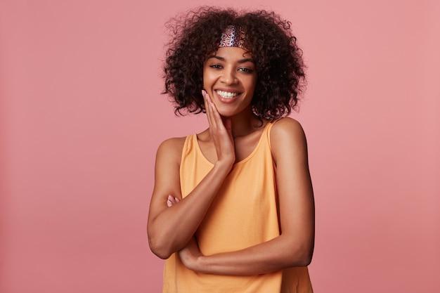 Heureuse jolie jeune femme brune bouclée avec une peau foncée portant une coiffure décontractée en position debout, touchant son visage avec paume surélevée et souriant sincèrement