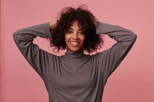 Heureuse jolie jeune femme brune à la peau foncée avec des cheveux courts bouclés posant en pull gris gorge, souriant largement et tenant les mains levées sur sa tête