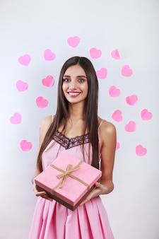 Heureuse jolie jeune femme brune tenant une boîte-cadeau et des coeurs roses