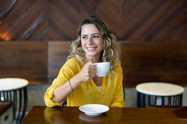 Heureuse jolie jeune femme buvant du thé au café