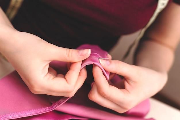 Heureuse jolie jeune femme couturière assise et coud sur machine à coudre sur mur léger. concept de couture, produits artisanaux.