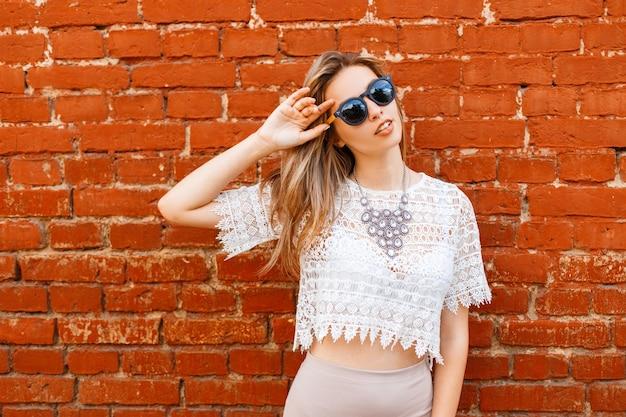 Heureuse jolie jeune femme hipster à lunettes de soleil dans un chemisier en dentelle blanche