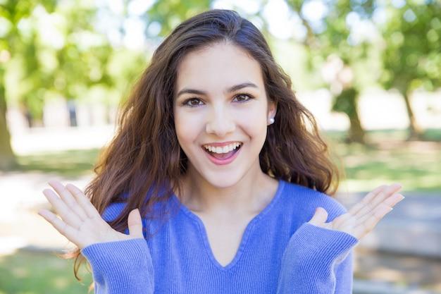 Heureuse jolie jeune femme levant les mains dans le parc