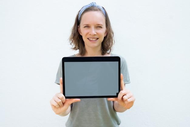 Heureuse jolie jeune femme montrant l'affichage de la tablette vierge