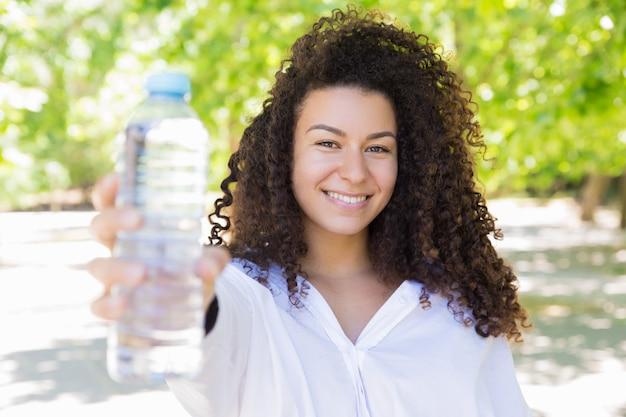 Heureuse jolie jeune femme montrant une bouteille d'eau dans le parc