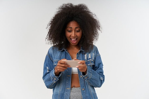 Heureuse jolie jeune femme à la peau foncée en haut blanc et manteau en jean posant sur un mur blanc avec un téléphone portable dans les mains, regardant l'écran et tapant un message avec un visage excité