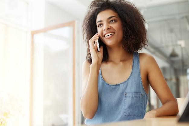 Heureuse joyeuse belle femme africaine souriante parlant au téléphone assis dans le café.
